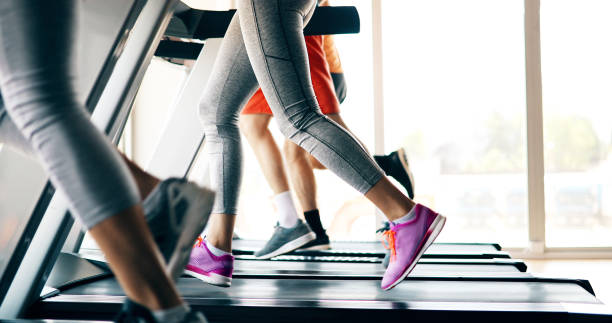 picture of people running on treadmill in gym - treadmill stock photos and pictures