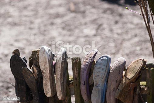955947208 istock photo Picture of poverty in old worn house slippers on wooden fence 947013880
