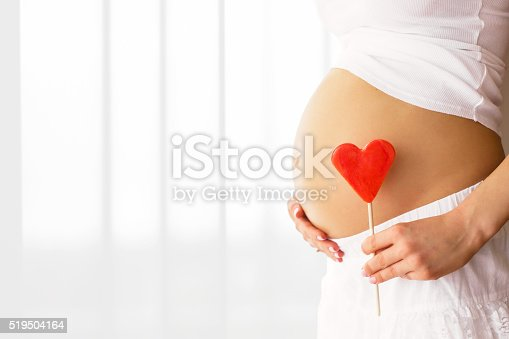 istock Picture of pregnant woman holding heart sign to one side 519504164