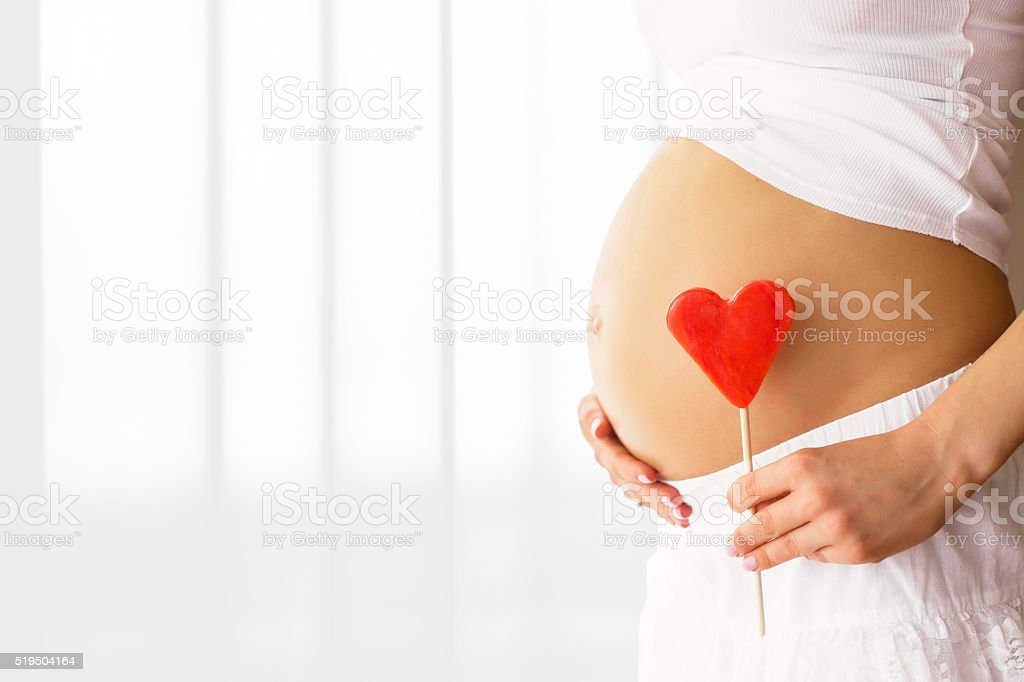 Picture of pregnant woman holding heart sign to one side stock photo