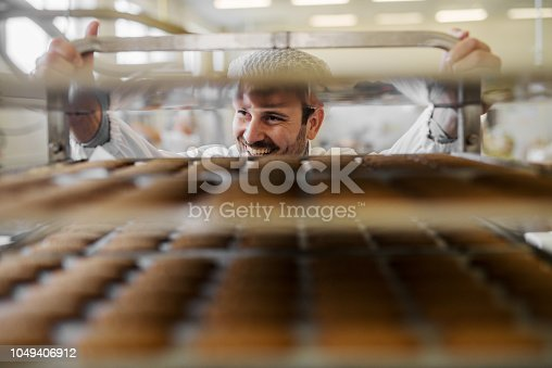 Picture of professional male baker man in white work uniform . Standing in front of the shelves full with fresh baked cookies.