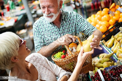 Picture of mature couple at marketplace buying vegetables