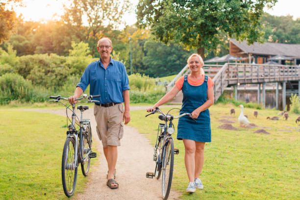Picture of senior couple walking with bicycles in the park at sunset. Picture of senior couple walking with bicycles in the park at sunset. Concept of active old people, travel, healthy and sustainable lifestyle, ecological transport. electric bike tour stock pictures, royalty-free photos & images