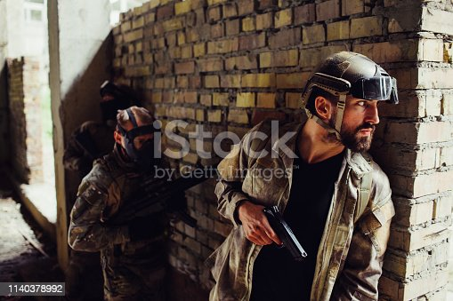 istock A picture of serious bearded man hiding behind wall and looking to the side. He has gun. Other two men in maska are standing behind him. They are waiting for his command to start a fight. 1140378992