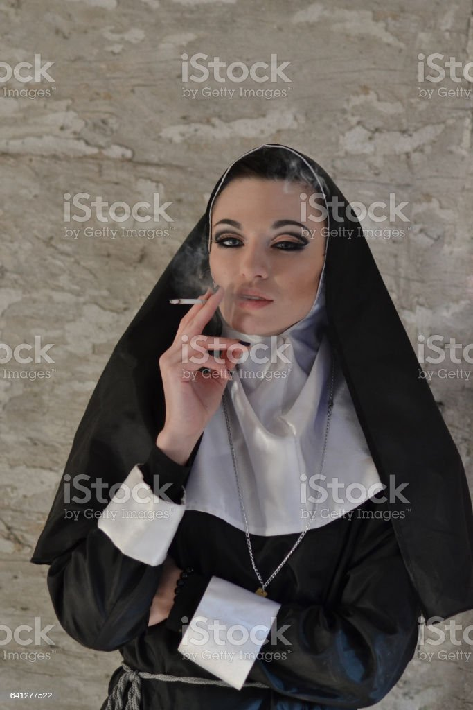 Picture of sexy beautiful nun with cigarette fog on background. Nun girl in the studio. Spoiled concept of religion. Cigarette. Halloween. Non-healthy lifestyle. No smoke. stock photo