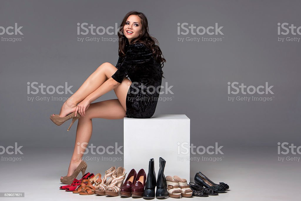picture of sitting woman trying on high heeled shoes stock photo