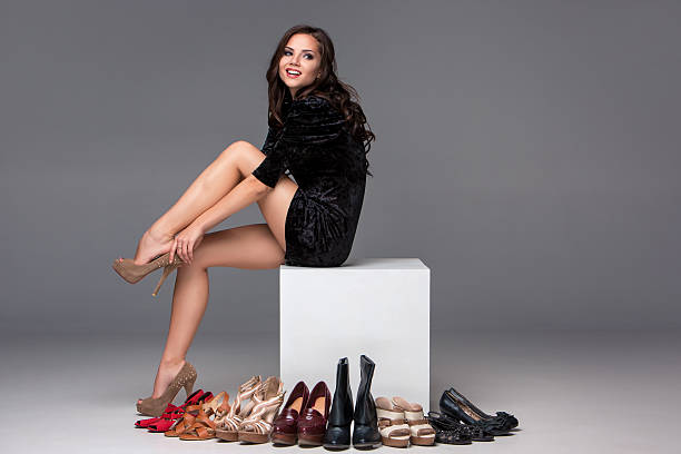 picture of sitting woman trying on high heeled shoes - human leg stock photos and pictures