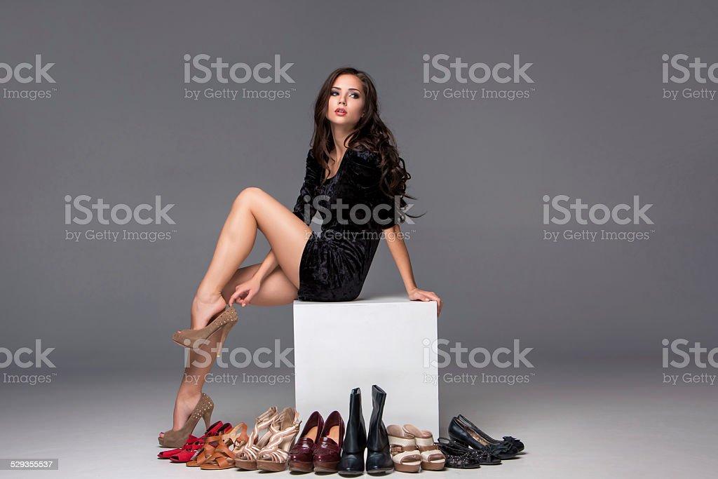 Cтоковое фото Картина сидящая женщина, пытаясь на высоких каблуках