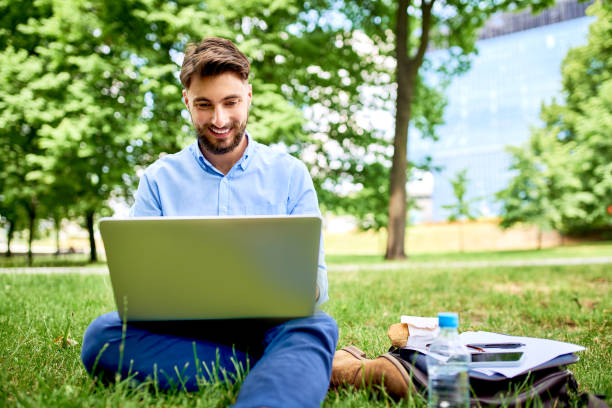 Picture of smiling young businessman working on laptop while having luch in the park stock photo
