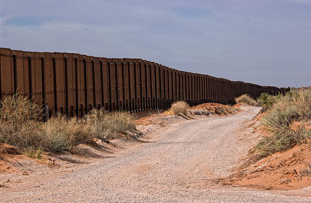 Picture of the Border Fence in New Mexico  Gravel road along the Border fence between New Mexico, USA and the northern state of Chihuahua, Mexico. international border barrier stock pictures, royalty-free photos & images