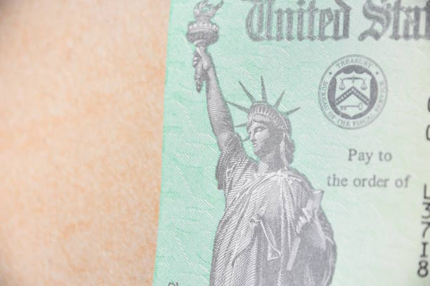 a picture of the statue of liberty on a government check - social security check stock photos and pictures