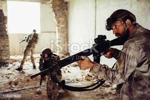 istock A picture of thhree warriors standing in different positions in one ruined room. Bearded guy holds rifle, the second one is standing in the middle of room while the third one is standing closer to window. 1140379032