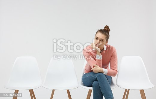 istock Picture of tired female candidate in casual pink sweater waiting for job interview in hall, sitting in line on chair, feeling bored 1001503094