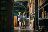 Picture of two business man standing in warehouse with helmets on their heads and celebrating great news about their business. Standing in big warehouse and looking happy and satisfied.