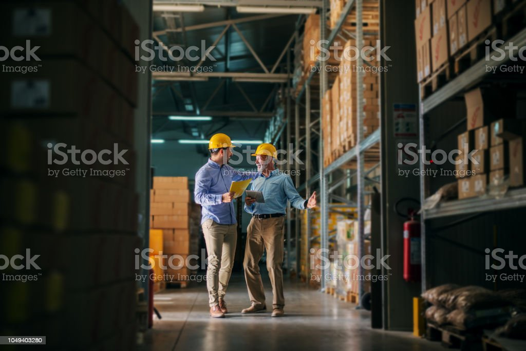 Picture of two business man standing in warehouse with helmets on their heads and celebrating great news about their business. Standing in big warehouse and looking happy and satisfied. stock photo