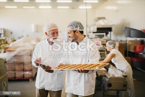 Picture of two employees in sterile clothes in food factory smiling and talking. Younger man is holding tray full of fresh cookies while the older is holding tablet and checking production line.