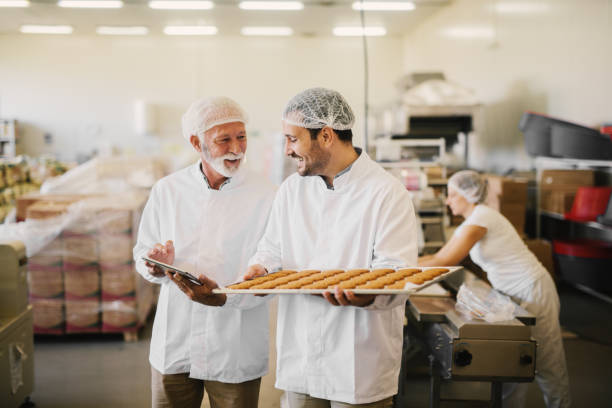 picture of two employees in sterile clothes in food factory smiling and talking. younger man is holding tray full of fresh cookies while the older is holding tablet and checking production line. - panetteria foto e immagini stock