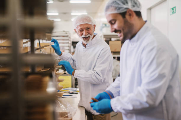 Picture of two male food factory employees in sterile clothes packing fresh made cookies and having fun. Picture of two male food factory employees in sterile clothes packing fresh made cookies and having fun. hair net stock pictures, royalty-free photos & images