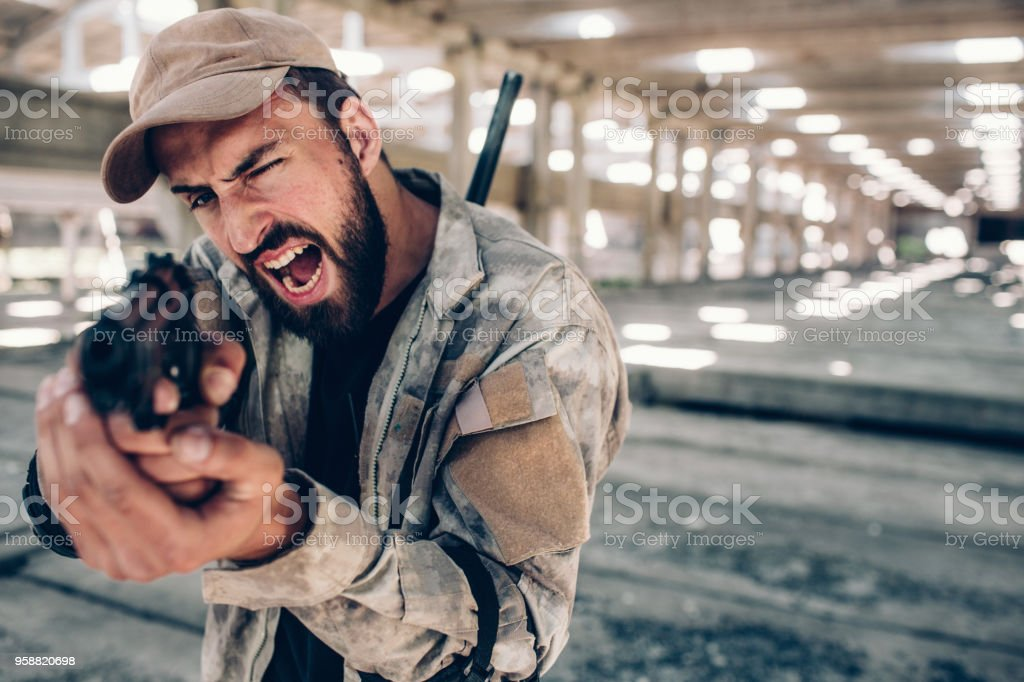 A picture of warrior screaming and yelling. He is taking aim by using small gun. Soldier is doing that with both hands. He is ready to shoot stock photo