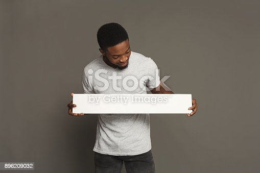 896826068 istock photo Picture of young african-american man holding white blank board 896209032