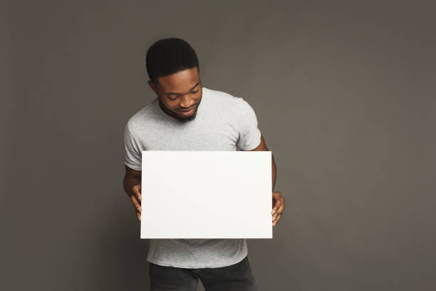 Picture of young african-american man holding white blank board stock photo