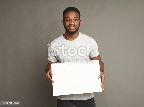 896826068 istock photo Picture of young african-american man holding white blank board 925781898