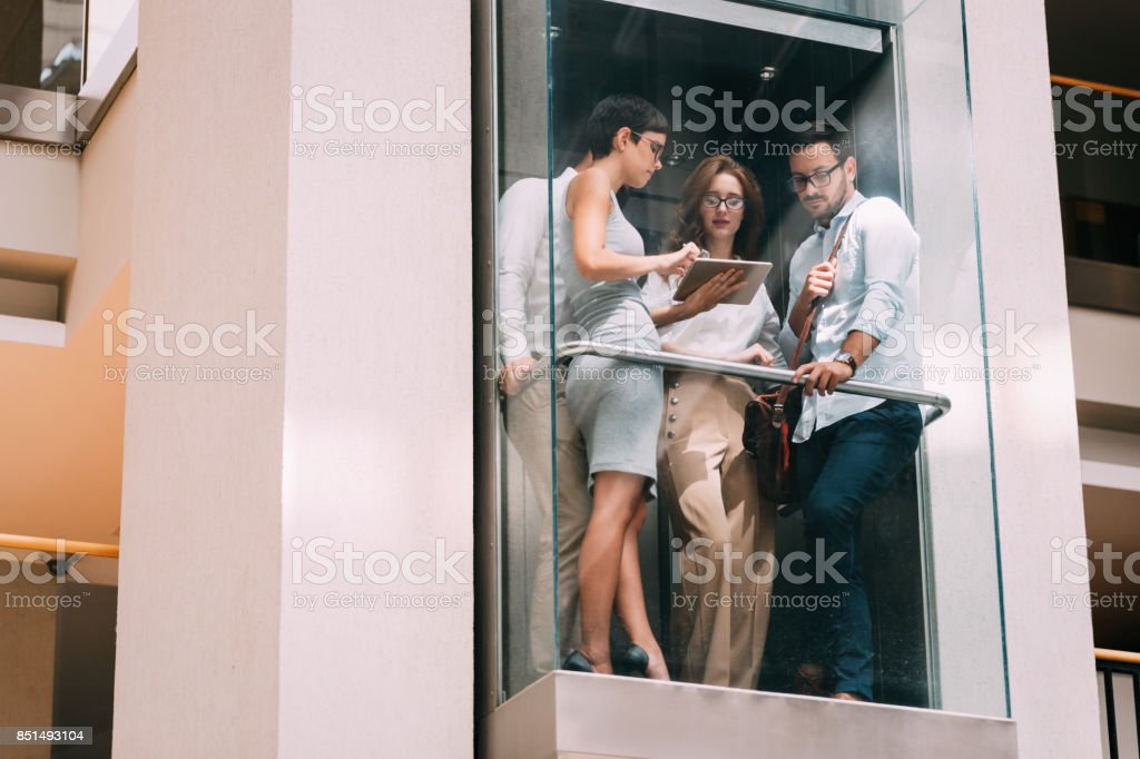 Picture of young businesspeople talking in elevator Picture of young attractive businesspeople talking in elevator Adult Stock Photo