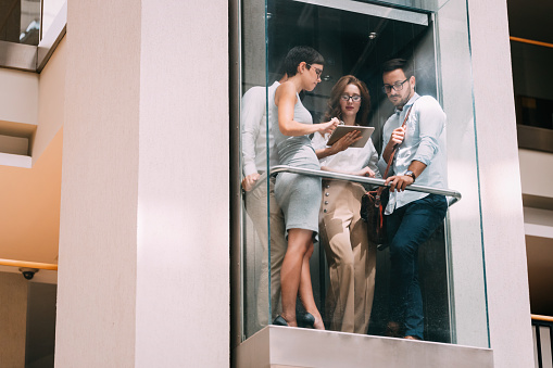 Picture Of Young Businesspeople Talking In Elevator Stock Photo - Download Image Now