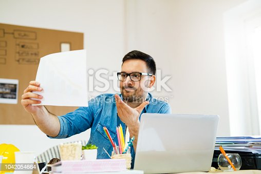 1129095769 istock photo Picture of young creative engineer sitting in his office and looking in some projects. 1042054664
