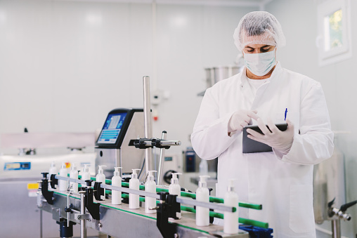 Picture of young man in sterile clothes using tablet . Controlling production line on factory. Bottles with cosmetic products on production line.