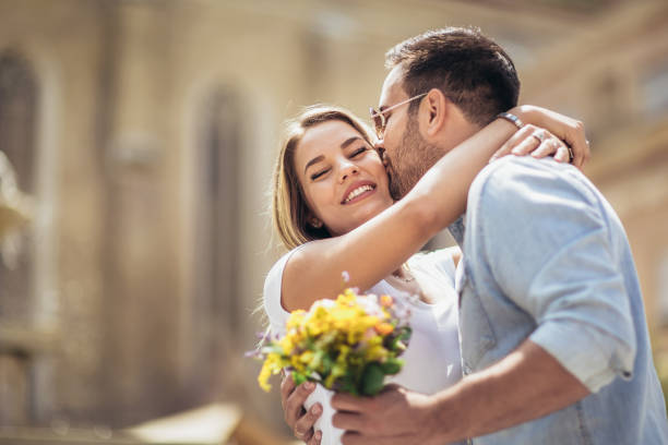 picture of young man surprising woman with flowers - falling in love stock pictures, royalty-free photos & images