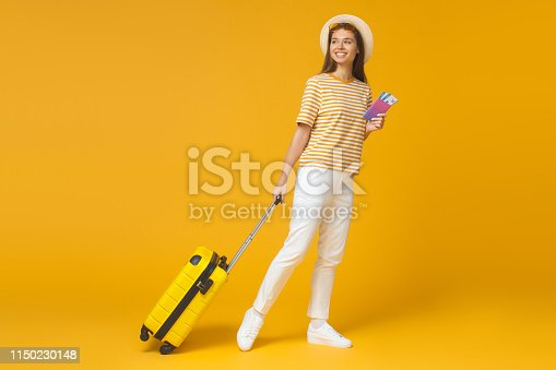 Picture of young woman dragging suitcase while walking with tickets to airplane, isolated
