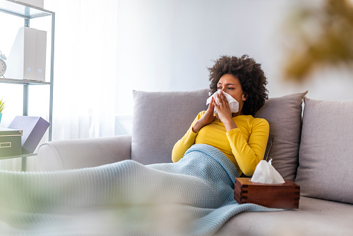 The sick woman, holding a handkerchief, sneezing and feeling freezing, lying on the bed, at home. Health problem. Sick African American woman lying on the sofa