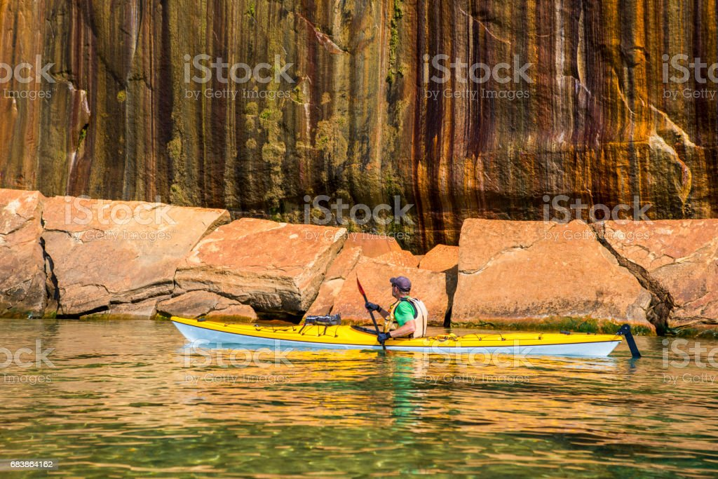 Pictured Rocks Kayaker Along Colored Cliffs stock photo