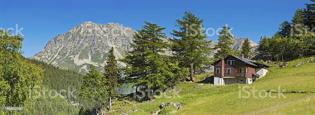 Picturesque Alpine chalet summer mountain meadow panorama stock photo