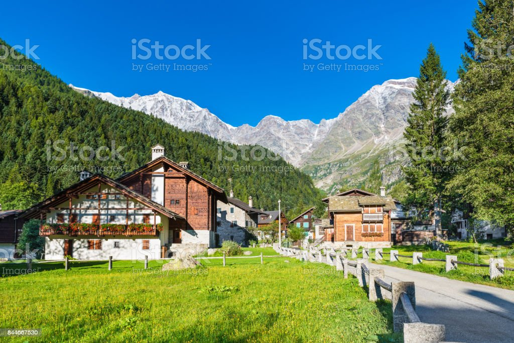 Picturesque and characteristic alpine village, Italy. Macugnaga (Staffa), little touristic village with wooden and stone houses at the foot of the east wall of Monte Rosa stock photo