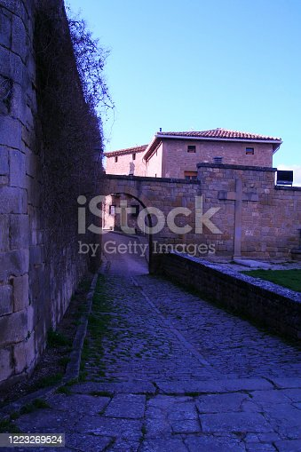 Picturesque and medieval small town street, cross made of stone, stone arch and blue sky