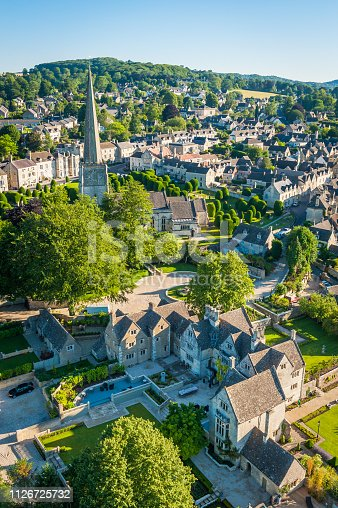 Aerial view over the iconic Cotswold village of Painswick, with its honey coloured limestone cottages deep in the bucolic countryside of Gloucestershire, UK, framed by vibrant green patchwork fields and clear blue summer skies.