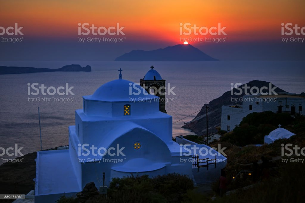 Picturesque Greek Church at the typical village of Plaka, Milos island, Greece, viewed at sunset stock photo