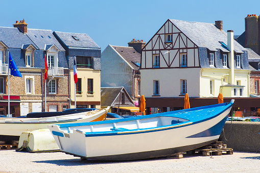 Picturesque landscape beautiful city of Etretat of Normandy, France. Fishing boats near country houses