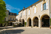 Monflanquin, France - April 6th, 2017: A picturesque corner of the idyllic central square in Monflanquin, Lot-et-Garonne, France. Monflanquin is a member of The Most Beautiful Villages of France (Les Plus Beaux Villages de France) association and is thought to be one the most historically intact examples of a medieval bastide town.