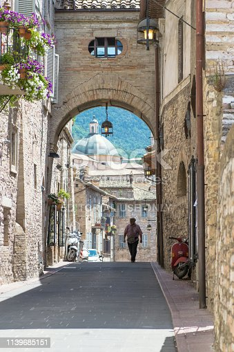 Assisi, Italy - July 28, 2017: Picturesque old street of the medieval Assisi with a male figure , Assisi, Umbria, Italy