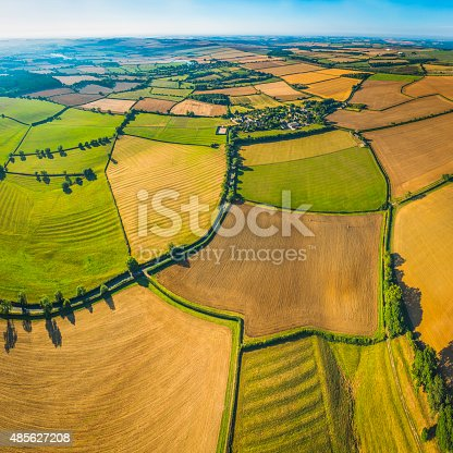 Aerial view over picturesque patchwork landscape of green pasture, lush meadows and golden wheat crop fields amongst the rolling hills and quiet valleys below blue summer skies. ProPhoto RGB profile for maximum color fidelity and gamut.