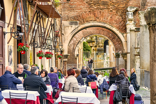 Rome, Italy, February 02 -- A typical restaurant of Italian and kosher cousins with the Roman temple of Portico d'Ottavia in background, the heart of the Jewish Ghetto of Rome. The iconic Jewish Quarter of Rome, the oldest ghetto in Europe, is famous for the presence of hidden alleys and small squares, where it is easy to find small restaurants of Italian and Jewish cuisine, and remarkable Roman archaeological remains of republic and imperial era, in an area of the city between the Capitoline Hill (Roman Capitol) and the River Tiber. Image in High Definition format.
