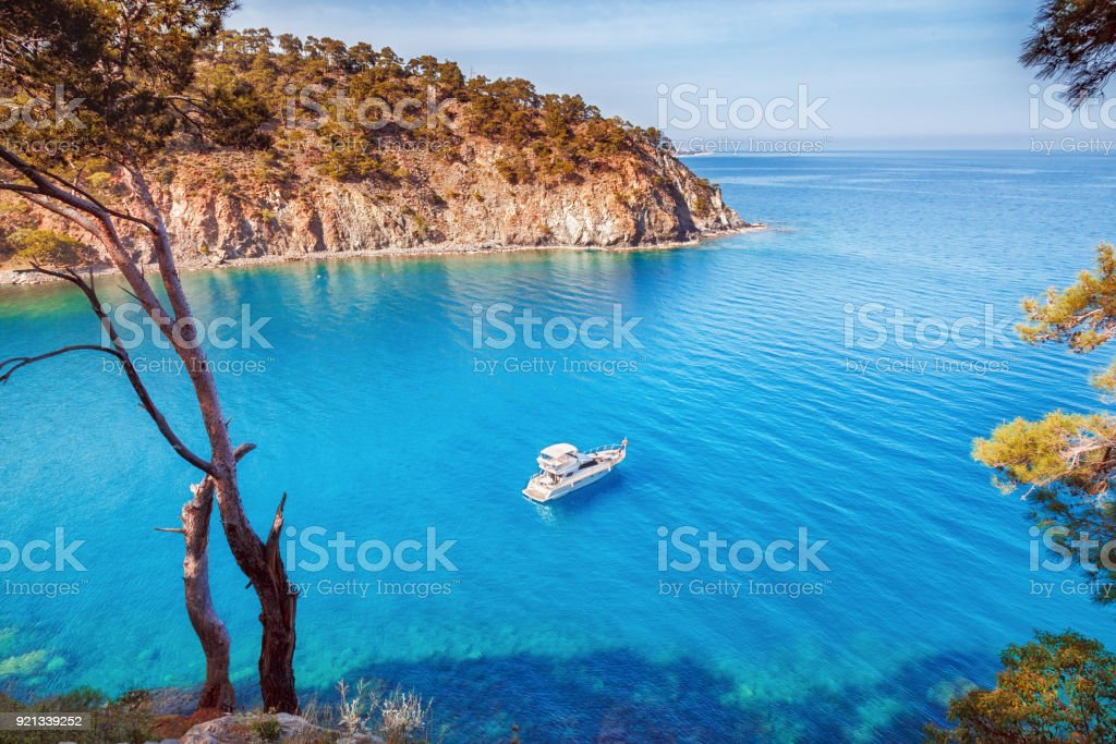 Picturesque scenery of coastline of Turkey on Mediterranean sea. Solitary luxury white yacht in the incredible bay. Summer vacation background. Location Antalya Turkey. stock photo