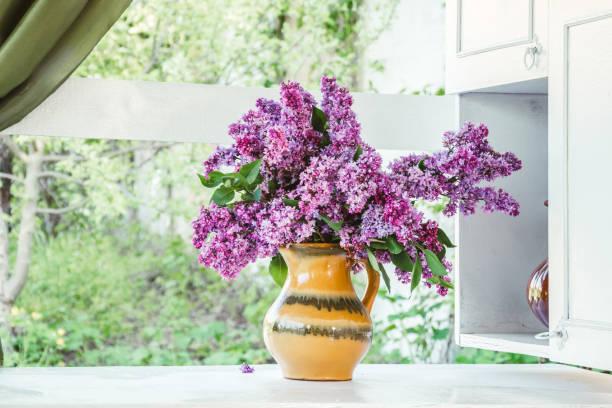 malerischer frühlingsstrauß mit lilien in einem rustikalen garten - küche lila stock-fotos und bilder