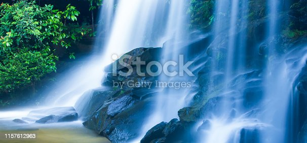 Picturesque tropical waterfall on summer morning, soft freshwater falling on layers of rocky steep and black stones. Phu Chong Nayoi, Thailand. Long exposure, motion blur.