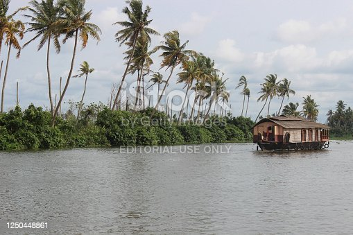 A Picturesque view of a sailing Houseboat ,coconut trees against clouds and the river in the Allapuzza backwaters of Kerala tourism in India.