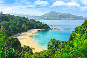 Exotic views through the jungle to uninhabited beach. Blue lagoon. Picturesque bay. Laem sing beach.