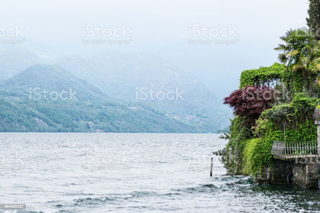 Picturesque view of the Alpine Lake Orta and garden of island San Giulio  (Isola di San Giulio) on a foggy day royalty-free stock photo